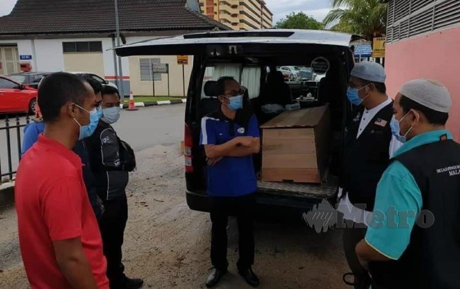 SKUAD Pengurusan Jenazah Malaysia berbincang sebelum menguruskan pengebumian jenazah pesakit Covid-19 di Tanah Perkuburan Islam Setali, Kuantan, Pahang, hari ini. FOTO ihsan Skuad Pengurusan Jenazah Malaysia.