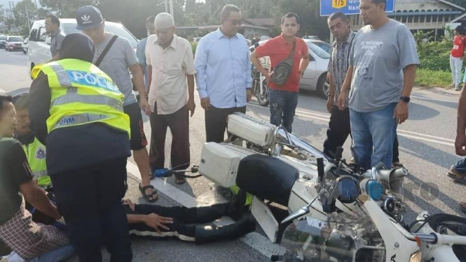 MUHAMMAD Sanusi (empat dari kanan) melihat keadaan anggota trafik yang cedera. FOTO Ihsan Pembaca