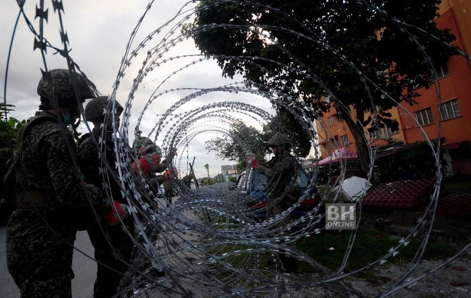 Anggota Angkatan Tentera Malaysia (ATM) melakukan kerja-kerja pemasangan kawat duri di sekitar Pangsapuri Taman Langat Utama dan Pangsapuri Taman Langat Murni, hari ini. - Foto BERNAMA